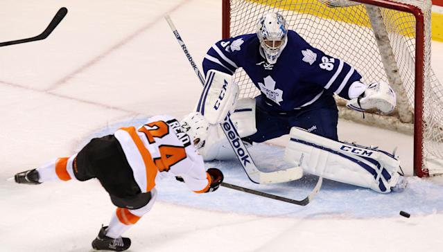 Philadelphia Flyers' Matt Read stretches to try and get the puck behind Maple Leafs' goalie Christopher Gibson during the third period of an NHL pre-season game, Sunday Sept. 15, 2013 in London, Ontario. (AP Photo/The Canadian Press, Dave Chidley)
