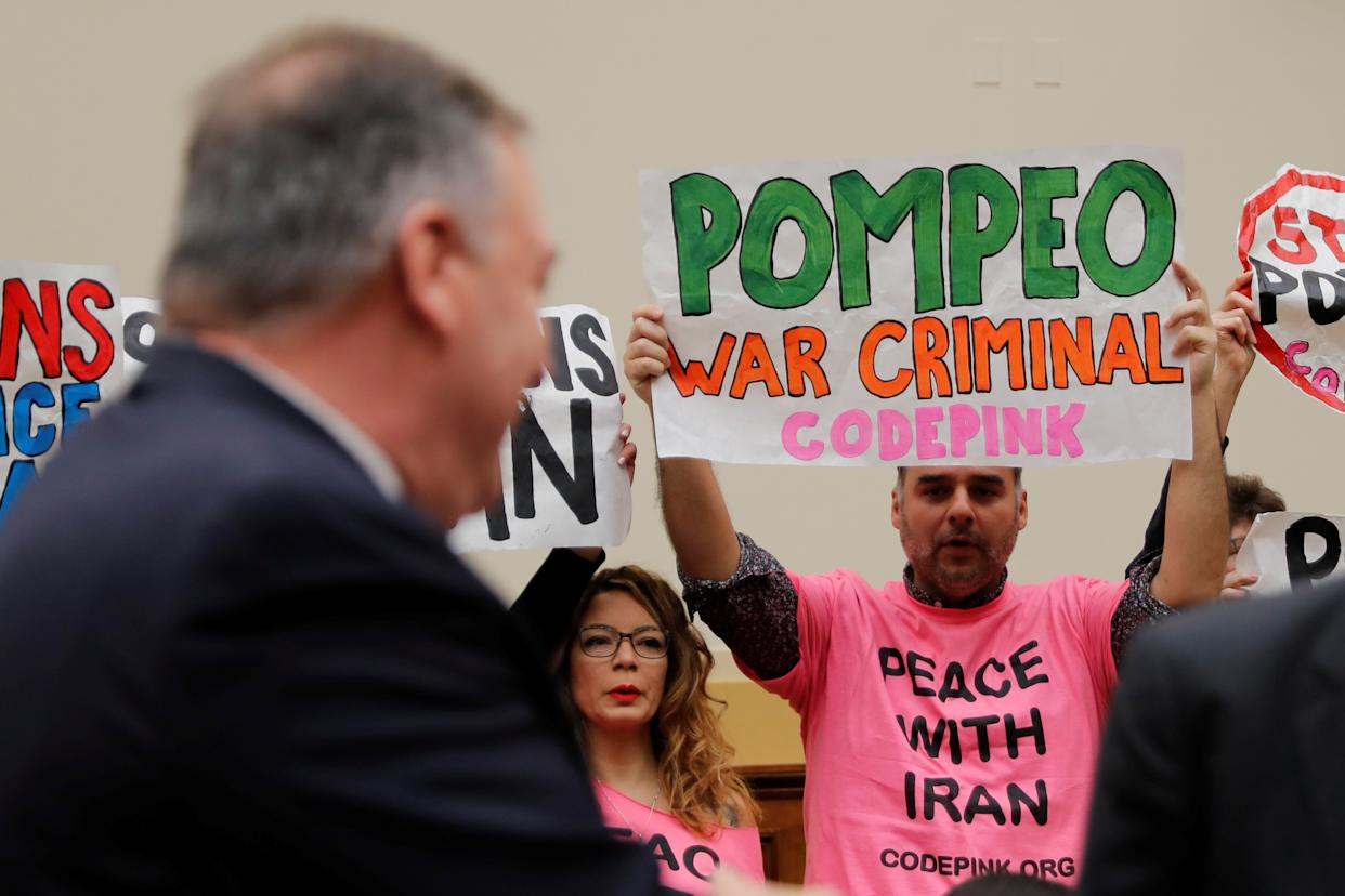 Protesters hold placards as Mike Pompeo attends a House Foreign Affairs Committee hearing