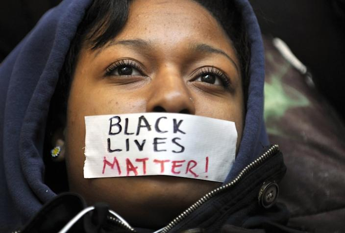 """Penn State student Zaniya Joe wears a piece of tape over her mouth that says """"Black Lives Matter"""" as she participates in a demonstration reacting to the events in Ferguson, Missouri. <span class=""""copyright"""">(Nabil K. Mark / Associated Press)</span>"""