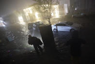 People use flashlights as they walk on flooded streets in search of their vehicle, Wednesday, Sept. 16, 2020, in Pensacola, Fla. Hurricane Sally made landfall Wednesday near Gulf Shores, Alabama, as a Category 2 storm, pushing a surge of ocean water onto the coast and dumping torrential rain that forecasters said would cause dangerous flooding from the Florida Panhandle to Mississippi and well inland in the days ahead. (AP Photo/Gerald Herbert)