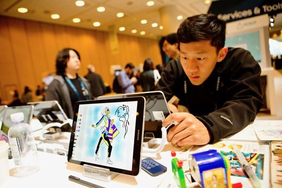 A Samsung tablet in the foreground with a person looking at a Samsung tablet in the background.