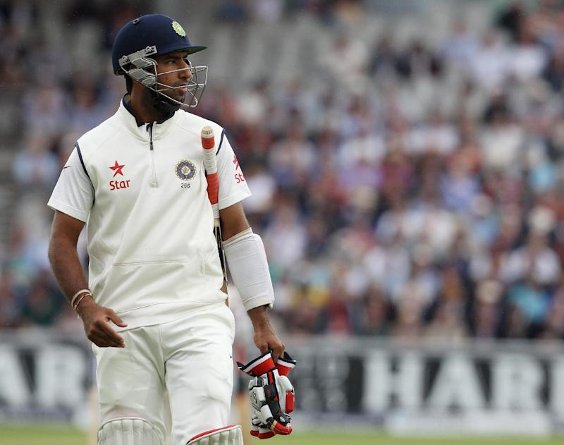 India's Cheteshwar Pujara walks back to the pavillion following his dismissal for no runs during the first day of the fourth cricket Test match between England and India at Old Trafford in Manchester on August 7, 2014