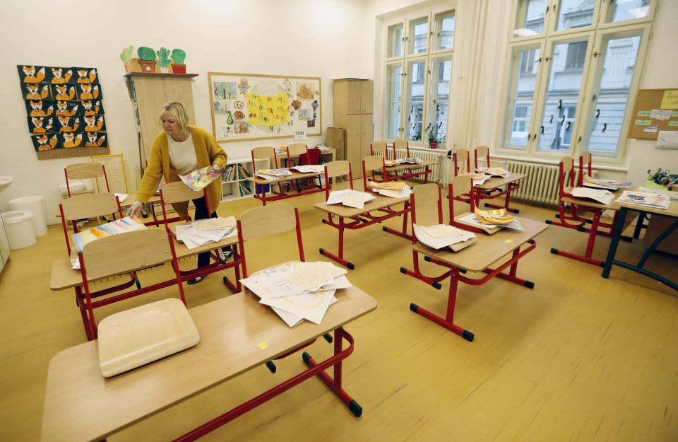 A teacher sorts drawings in an empty classroom at a closed school in Prague, Czech Republic, Wednesday, Oct. 14, 2020. Amid widespread efforts to curb the new wave of coronavirus infections in one of the hardest hit European countries, the Czech Republic closed again all its schools on Wednesday. (AP Photo/Petr David Josek)