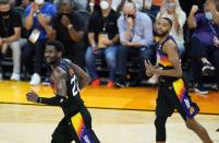 Phoenix Suns center Deandre Ayton (22) and Suns forward Mikal Bridges, right, run down the court after a Suns score against the Milwaukee Bucks during the second half of Game 1 of basketball's NBA Finals, Tuesday, July 6, 2021, in Phoenix. (AP Photo/Ross D. Franklin)