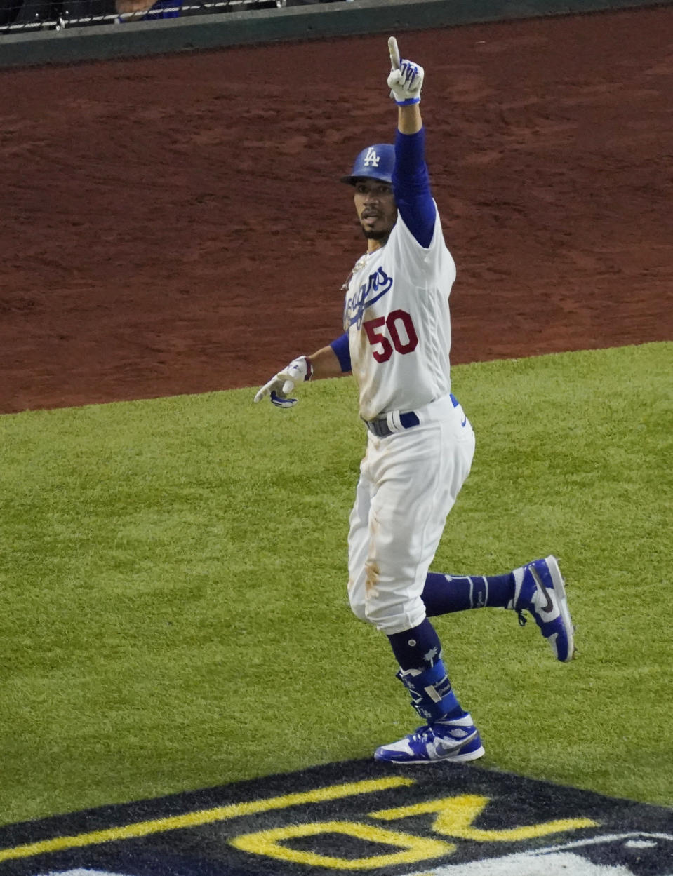 Los Angeles Dodgers' Mookie Betts celebrates a home run against the Tampa Bay Rays during the sixth inning in Game 1 of the baseball World Series Tuesday, Oct. 20, 2020, in Arlington, Texas. (AP Photo/Sue Ogrocki)