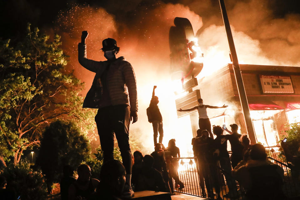 In this image released by World Press Photo, Thursday April 15, 2021, by John Minchillo, Associated Press, part of a series titled Minneapolis Unrest: The George Floyd Aftermath, which won third prize in the Spot News Stories category, shows Protesters raise their fists in defiance outside a burning fast-food restaurant near the precinct station of the officers who arrested Floyd, in Minneapolis, Minnesota, USA, on May 29, 2020. (John Minchillo, Associated Press, World Press Photo via AP)
