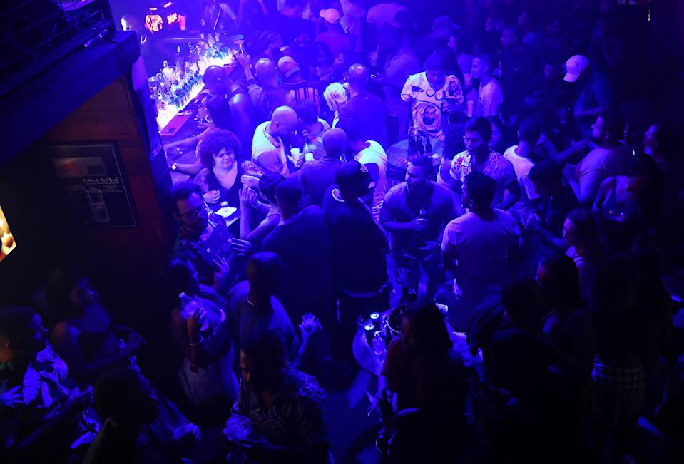 RIO DE JANEIRO, BRAZIL - MAY 23: Revelers gather in a nightclub in the early morning hours amid the COVID-19 pandemic on May 23, 2021 in Rio de Janeiro, Brazil. COVID-19 has now claimed more than 1 million lives in Latin America and the Caribbean, with nearly half of those deaths in Brazil. Only three percent of the population of Latin America have been fully vaccinated against COVID-19. Health experts are warning that Brazil should brace for a new surge of COVID-19 amid a slow vaccine rollout and relaxed restrictions. The state of Sao Paulo has registered more than 3 million cases of COVID-19 and more than 100,000 deaths. Nearly 450,000 people have died in Brazil by COVID-19, second only to the U.S.  (Photo by Mario Tama/Getty Images)