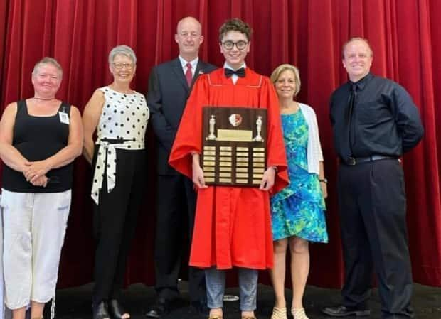 Charlottetown Rural High School graduate Brandon MacKinnon poses with the valedictorian plaque. MacKinnon delivered the valedictory address at 11 separate ceremonies so each gathering would be small enough to meet Prince Edward Island public health guidelines during the pandemic.  (Brandon MacKinnon/Instagram - image credit)