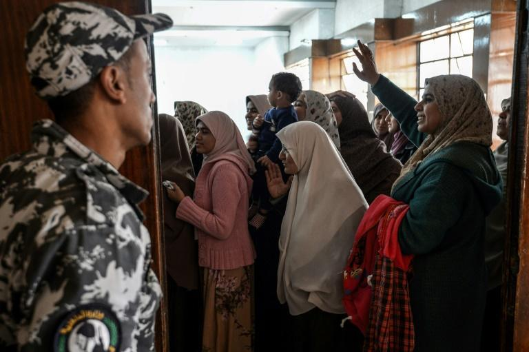Relatives of Muslim Brotherhood members facing the death penalty try to wave to their loved ones at a hearing in December 2018