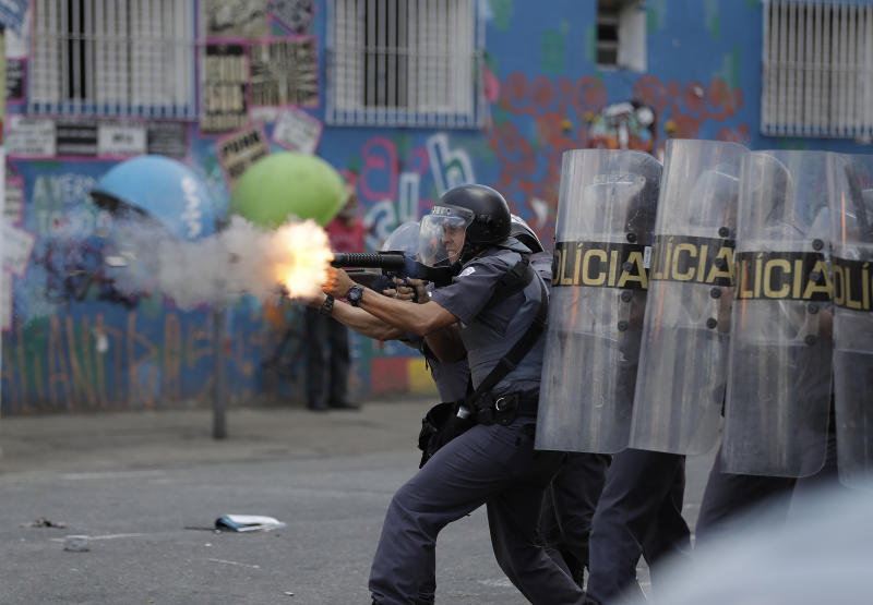 "A policeman fires tear gas during clashes with drug addicts in an area popularly known as ""Crackland"" in downtown Sao Paulo, Brazil, Thursday, Feb. 23, 2017. According with the police the clash start when two suspects were detained for stealing a mobile phone. (AP Photo/Andre Penner)"