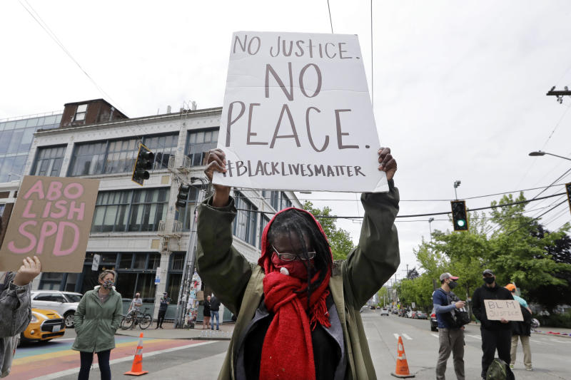 Demonstrator Kathy Woodward holds up a sign as she protests police actions, Thursday, June 4, 2020, in Seattle, following protests over the death of George Floyd, a black man who died after being restrained by Minneapolis police officers on May 25. Seattle's police chief says officers' badge numbers will be prominently displayed following complaints that black bands obscured the digits. (AP Photo/Elaine Thompson)
