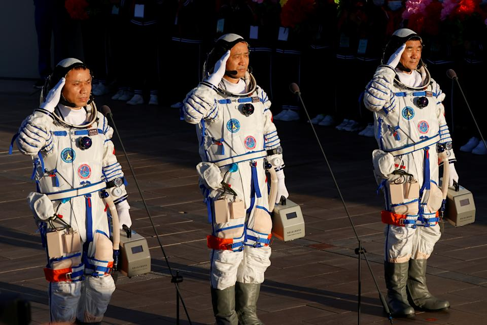 Chinese astronauts Tang Hongbo, Nie Haisheng and Liu Boming salute before the launch of the Long March-2F Y12 rocket, carrying the Shenzhou-12 spacecraft and the three astronauts, from Jiuquan Satellite Launch Center for China's first manned mission to build its space station, near Jiuquan, Gansu province, China June 17, 2021.   REUTERS/Carlos Garcia Rawlins