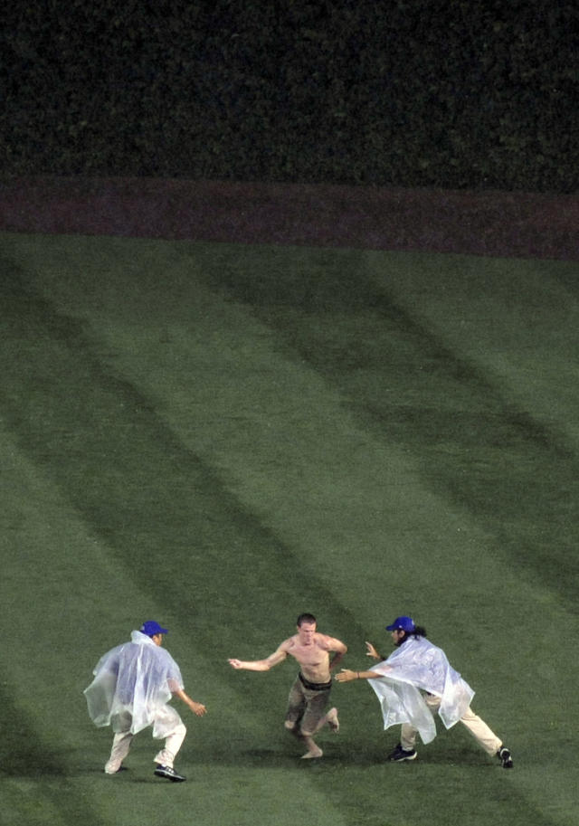 A fan, center, runs out on the field during a rain delay before a baseball game between the Chicago Cubs and the Pittsburgh Pirates in Chicago, Saturday, June 21, 2014. (AP Photo/Paul Beaty)