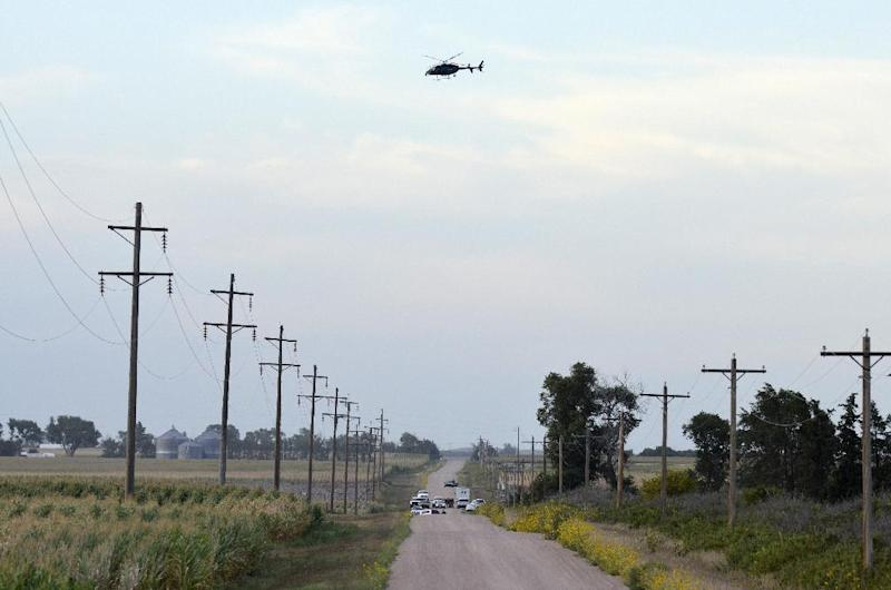 In this photo provided by the Imperial Republican law enforcement officials gather on a county road northwest of Imperial, Neb., early Sunday, Aug. 25, 2013, as a Nebraska State Patrol helicopter scours nearby corn fields in search of a Lincoln, Neb., man suspected of kidnapping his wife Saturday. Dwayne Lawrence eventually released his wife, Julie Hanes, unharmed, but then shot and killed himself. (AP Photo/Imperial Republican, Russ Pankonin)