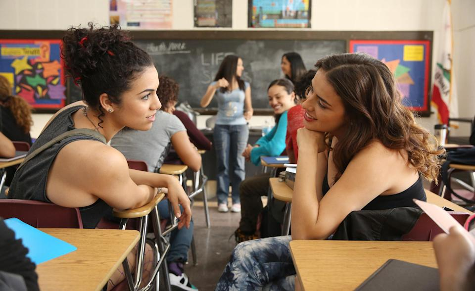 Andrea Sixtos and Vannessa Vasquez sitting in a classroom and talking to each other (Season 2)