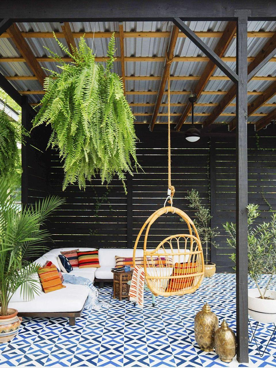 """<p>Turning an empty backyard corner into paradise is easier than you may think. A colorful rug, a floating couch and plants pull together a space, but it'll be a porch swing that steals the show. </p><p><strong>RELATED:</strong> <a href=""""https://www.goodhousekeeping.com/home/gardening/g1809/decor-ideas-deck-porch/"""" rel=""""nofollow noopener"""" target=""""_blank"""" data-ylk=""""slk:Decor Tips for Your Patio or Backyard"""" class=""""link rapid-noclick-resp"""">Decor Tips for Your Patio or Backyard</a></p>"""