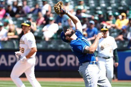 Jun 9, 2018; Oakland, CA, USA; Kansas City Royals first baseman Mike Moustakas (8) catches the ball for an out against Oakland Athletics first baseman Matt Olson (28) during the seventh inning at Oakland Coliseum. Mandatory Credit: Kelley L Cox-USA TODAY Sports
