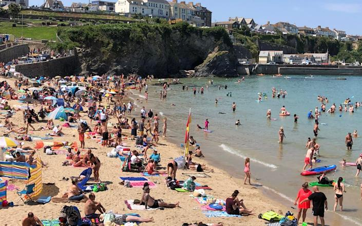 Holidaygoers in Cornwall enjoy the sunny weather on Newquay's Towen beach on 20 July 2021 - Jam Press/Jam Press