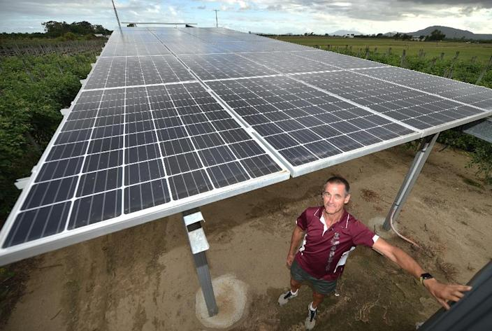 Australian farmer Denis Couture stands under solar panels on his farm outside of Bowen, part of his effort to move away from using environmentally damaging fossil fuels -- like coal from a nearby plant -- on his land (AFP Photo/PETER PARKS)