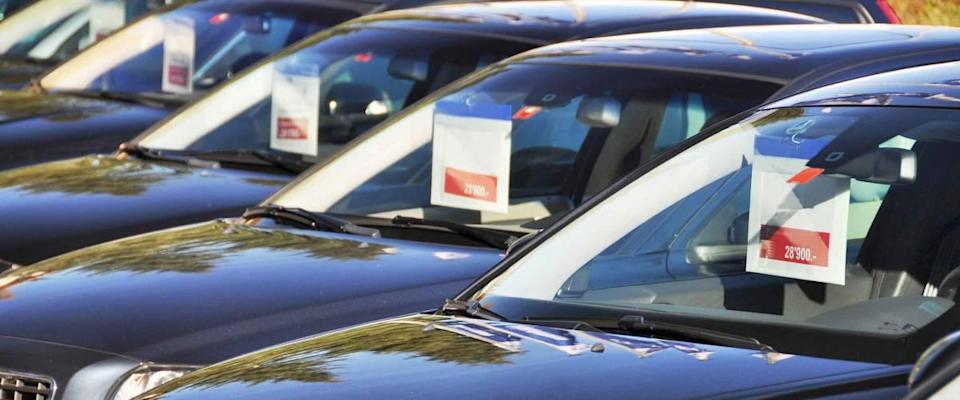 Cars for sale with signs hanging from rearview mirror