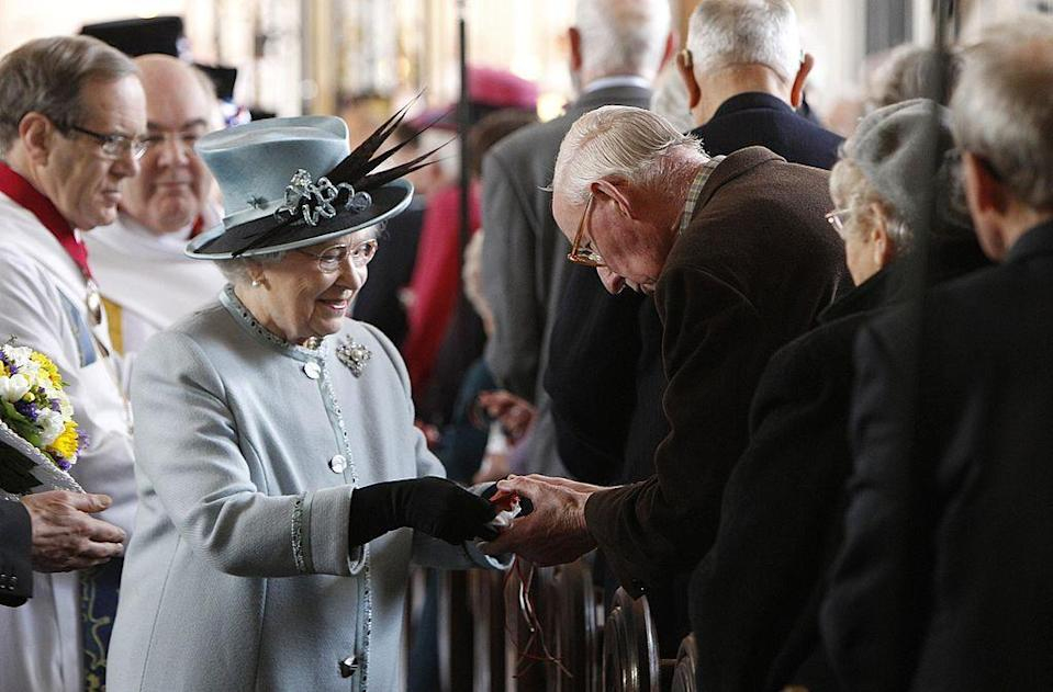 <p>Here, she hands out money at the Derby Cathedral in Derby, United Kingdom.</p>