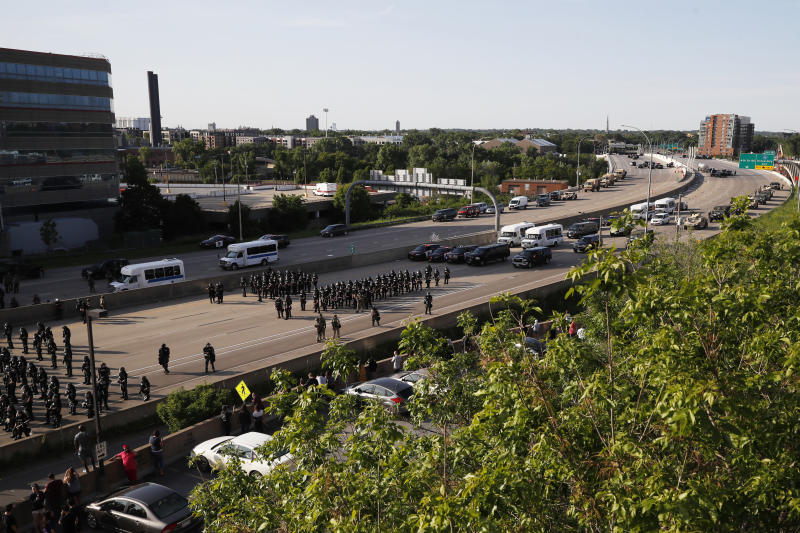 A police force prepares to clear an interstate of demonstrators Sunday, May 31, 2020, in Minneapolis. Protests continued following the death of George Floyd, who died after being restrained by Minneapolis police officers on Memorial Day. (AP Photo/John Minchillo)