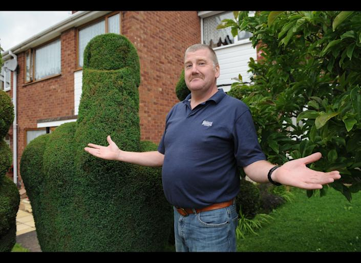 A bush carved into the shape of a middle-finger has landed a gardener into trouble after somebody failed to share his humour over the shrub. The council received a complaint about the shaped bush eight years after it was carved by Richard Jackson, 53, in his front garden. Despite only receiving one complaint, the council have since contacted Richard to alter the bush as it is considered a public offence. But Richard, from Tamworth, Staffs, said his neighbours are backing his pledge to keep the bush and they have even began a Save the Bush campaign to support him. Credit: Caters News