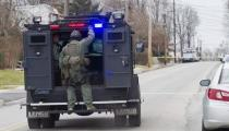 Police SWAT teams search outside a home in a suburb of Philadelphia where a suspect in five killings was believed to be barricaded in Souderton, Pennsylvania, December 15, 2014.REUTERS/Brad Larrison