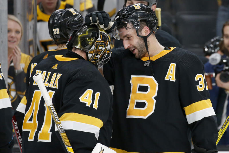 Boston Bruins center Patrice Bergeron (37) congratulates goaltender Jaroslav Halak (41) after beating the Pittsburgh Penguins in an NHL hockey game, Thursday, Jan. 16, 2020, in Boston. (AP Photo/Mary Schwalm)