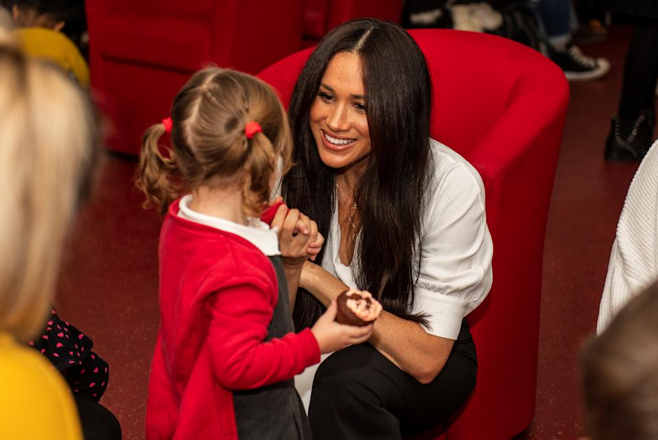 Poppy Dean gives a cake to Britain's Meghan, Duchess of Sussex during a coffee morning with families of deployed Army personnel at Broom Farm Community Centre in Windsor, Britain November 6, 2019. Picture taken November 6, 2019. Sgt Paul Randall/MoD/Handout via REUTERS  THIS IMAGE HAS BEEN SUPPLIED BY A THIRD PARTY.