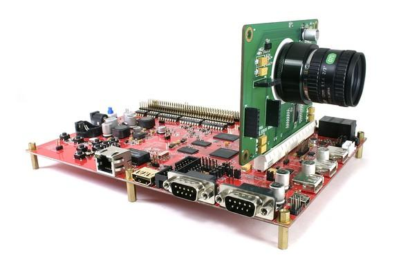 Camera attached to green circuit board, which is further attached to red motherboard.