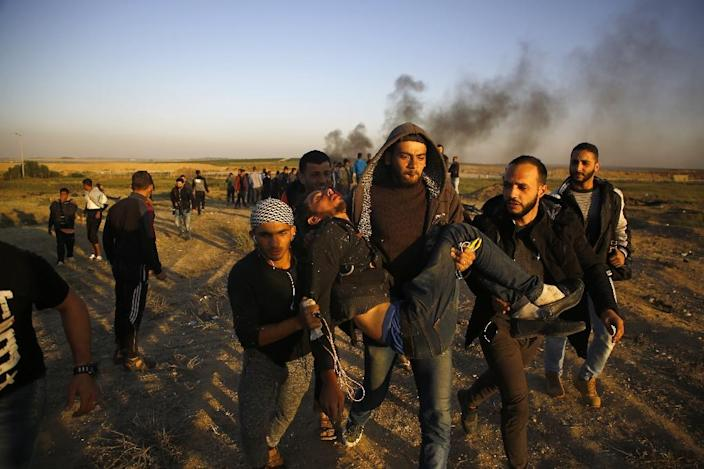 Palestinian protesters carry an injured man during clashes with Israeli forces along the border with Israel, east of Gaza City on April 1, 2018 (AFP Photo/Mohammed ABED)