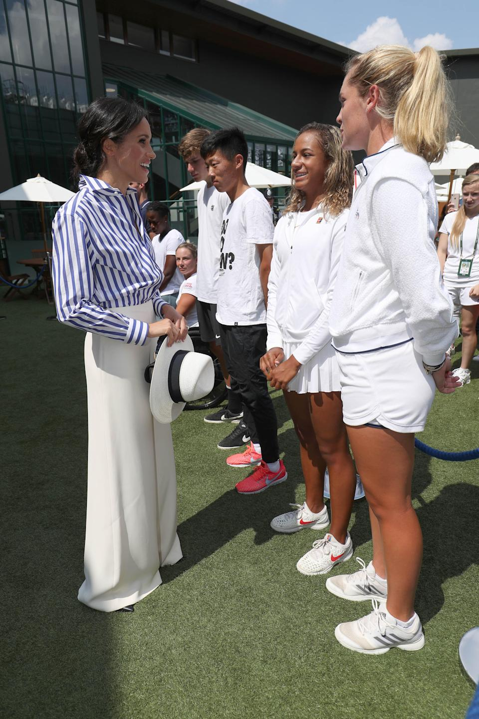 <p>For her debut Wimbledon appearance as a royal – and first solo appearance with the Duchess of Cambridge – Meghan donned a striped shirt and wide-leg trousers from Ralph Lauren. The Duchess finished the look with a low bun and a wide-brim hat, which she didn't wear but held. <em>[Photo: Getty]</em> </p>