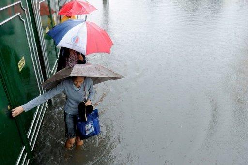 Pedestrians walk through floodwaters in Manila