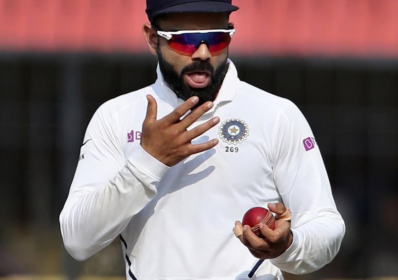 In this Nov. 16, 2019, file photo, India's captain Virat Kohli shines the ball during their cricket test match against Bangladesh in Indore, India. A move to ban the use of saliva to shine a cricket ball because of the danger of transmitting Covid-19 may force bowlers to relearn or reinvent one of the sport's most prized but troublesome skills. (AP Photo/Aijaz Rahi, FILE)