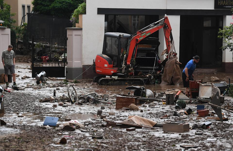 Residents look at debris in the muddy streets, following flood waters in a street in the town of Ahrweiler-Bad Neuenahr, western Germany, on July 15, 2021. - Heavy rains and floods lashing western Europe have killed at least 45 people in Germany and left around 50 missing, as rising waters led several houses to collapse. (Photo by Christof STACHE / AFP) (Photo by CHRISTOF STACHE/AFP via Getty Images)