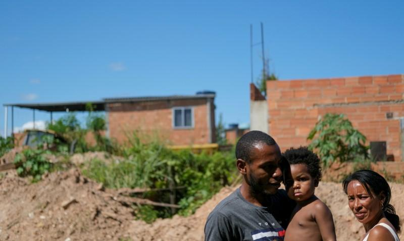Garbage collectors Adilson Farias, 31 (L) and his wife Rosana de Paula, 37, who work with Coopama, are pictured with their grandchild Ana Mikaely, 3, in Duque de Caxias near Rio de Janeiro