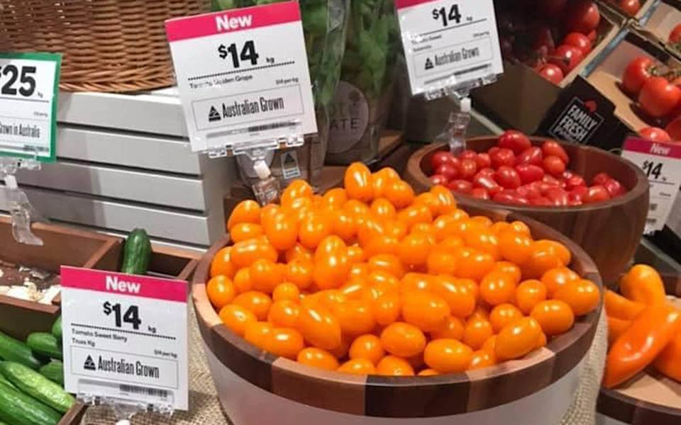 A shopper's photo shows a display of loose tomatoes.