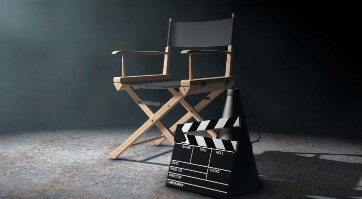 A director's chair, megaphone and movie clapper are arranged in a dramatically lit room.