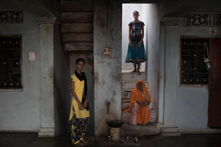 <p>Meena Lohar (21), in blue, stands on the stairs. She was married when she was 14 and later she managed to get a divorce. The husband lied about his age (he was much older) and her parents helped her to get a separation. In yellow, Vaishali (19). Her father arranged her wedding when she was younger, but she didn't accept and, with the help of her mother and a local NGO, made her father change his mind. Meena's grandmother sits on the stairs, she was also a child bride a long time ago. Changedi, Udaipur, Rajasthan, India, July 2016. (Photo: Rafael Fabrés) </p>
