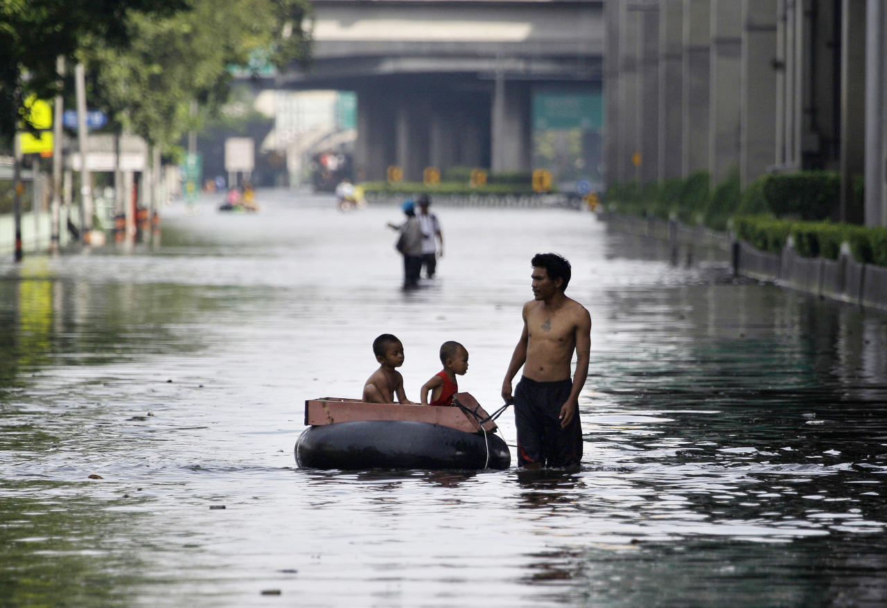 A Thai man pulls an improvised float to ferry children along flooded streets at the Lad Phrao district in Bangkok, Thailand, Saturday, Nov. 5, 2011. Thailand's record floods continued to creep towards inner Bangkok. (AP Photo/Aaron Favila)