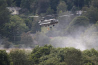 """An RAF Chinook helicopter drops aggregate to help shore up a reservoir at risk of collapse, threatening to engulf the town of Whaley Bridge in the Peak District, England, Friday, Aug. 2, 2019. A British military helicopter has dropped sandbags to shore up a reservoir wall as emergency services worked frantically to prevent a rain-damaged dam from collapsing. Engineers say they remain """"very concerned"""" about the integrity of the 19th-century Toddbrook Reservoir, which contains around 1.3 million metric tons (1.5 million (U.S tons) of water. (AP Photo/Jon Super)"""