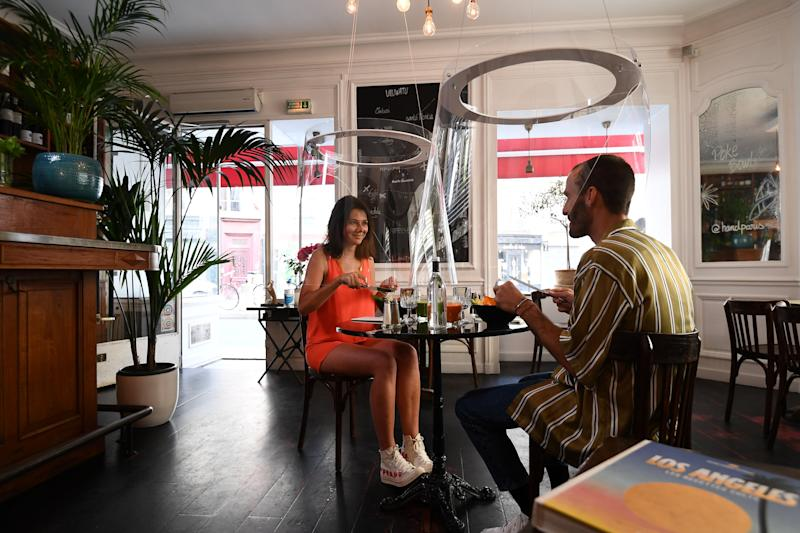 A couple has a lunch under plexiglass protection designed by Christophe Gernigon at the H.A.N.D restaurant, on May 27, 2020 in Paris, as France eases lockdown measures taken to curb the spread of the COVID-19 pandemic, caused by the novel coronavirus. (Photo by ALAIN JOCARD / AFP) (Photo by ALAIN JOCARD/AFP via Getty Images)