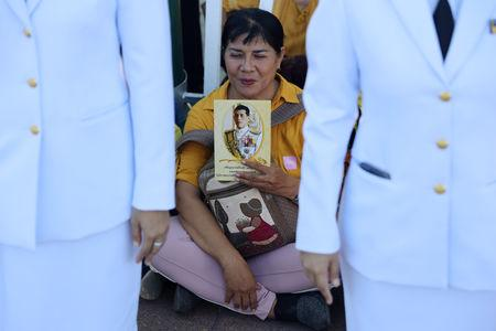 A woman holds an image of King Maha Vajiralongkorn during his coronation in Bangkok, Thailand, May 4, 2019. REUTERS/Athit Perawongmetha