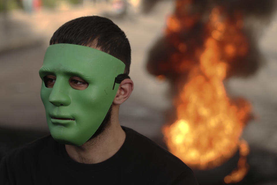 A protester wears a green mask, as other burn tires to block a road, in Beirut, Lebanon, Thursday, March 4, 2021. Lebanon has been hit by one crisis after another, with widespread protests against the country's corrupt political class breaking out in October 2019. (AP Photo/Bilal Hussein)