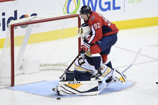 Washington Capitals center Evgeny Kuznetsov (92), of Russia, battles for the puck against Buffalo Sabres goaltender Carter Hutton (40) during the third period of an NHL hockey game, Saturday, Dec. 15, 2018, in Washington. (AP Photo/Nick Wass)