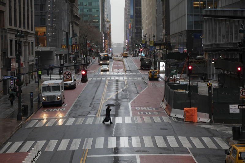 FILE - In this March 23, 2020, file photo, a commuter crosses 42nd Street in front of Grand Central Terminal during morning rush hour, in New York. (AP Photo/Mark Lennihan, File)