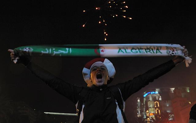 AN Algerian supporter celebrates their victory after the World Cup qualifying playoff second leg soccer match against Burkina Faso, in Algiers, Tuesday, Nov. 19, 2013. Algeria won 1-0 to qualify for the 2014 World Cup in Brazil. (AP Photo/Sidali Djarboub)