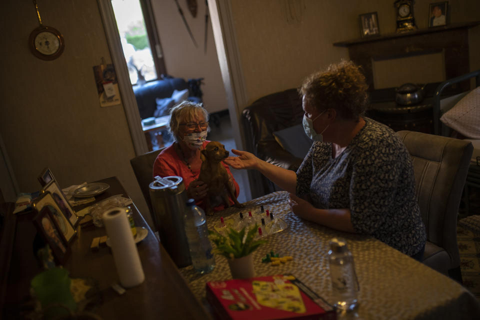 Home care worker Rosalinda De Pooter, right, wearing a face mask to protect against coronavirus, pets her client Josephine Claes' dog, as they play a table game during a partial lockdown against the spread of COVID-19 in Booischot, Belgium, Monday, April 27, 2020. (AP Photo/Francisco Seco)