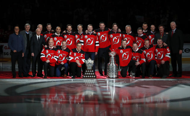 Former New Jersey Devils pose at center ice during a ceremony to honor the 2000 Stanley Cup team Saturday, Feb. 1, 2020, in Newark, N.J. (AP Photo/Noah K. Murray)